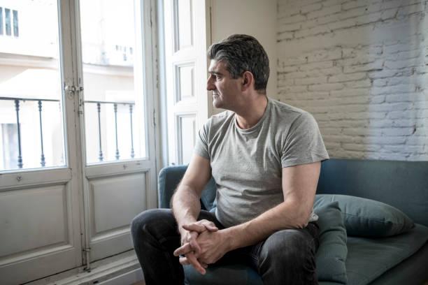 40er oder 50er Jahren traurig und besorgt Mann mit grauen Haaren, die zu Hause sitzen Sofa suchen, depressiv und verschwendet in Traurigkeit Gesichtsausdruck in Depressionen und Leben Probleme-Konzept – Foto