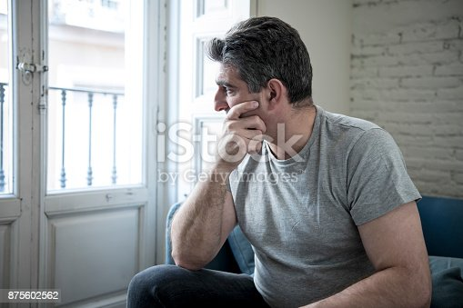 istock 40s or 50s sad and worried man with grey hair sitting at home couch looking depressed and wasted in sadness face expression in depression and life problems concept 875602562