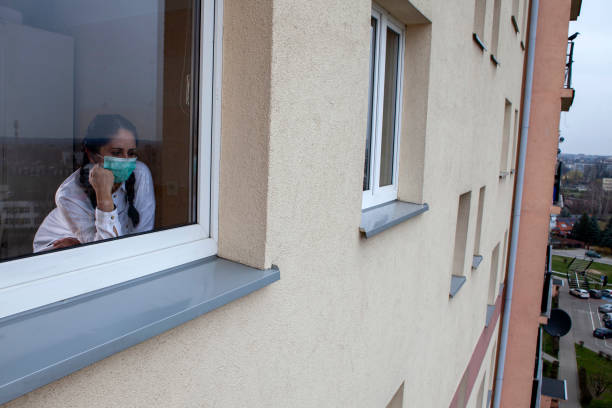 A 40-year-old woman wearing a protective mask is looking out of the window. Home quarantine for 14 days due to the coronavirus COVID-19 epidemic. A 40-year-old woman wearing a protective mask is looking out of the window. Home quarantine for 14 days due to the coronavirus COVID-19 epidemic. quarantine stock pictures, royalty-free photos & images