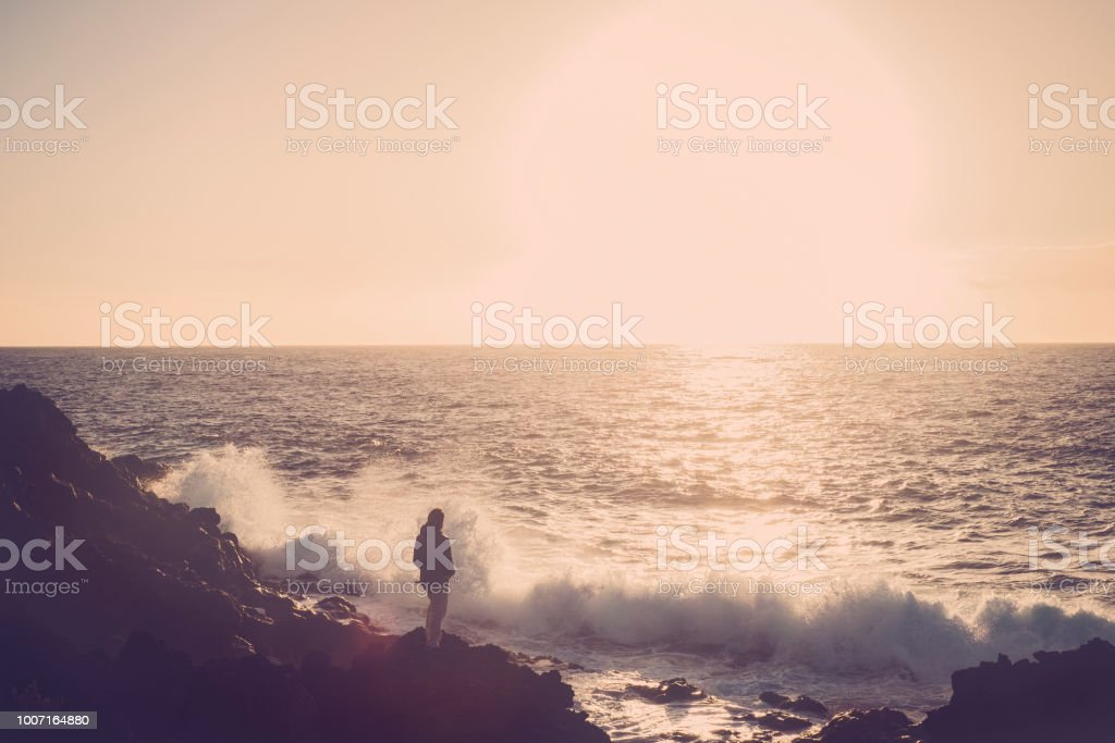 45-year-old man watches the sea and the waves at sunset, relaxing and reflecting about the life. travel and vacation concept. landscape with ocean and horizon and sunlight stock photo