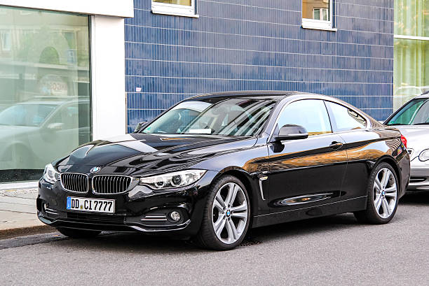 BMW F32 4-series Dresden, Germany - July 20, 2014: Black sports car BMW F32 4-series is parked at the city street. touring car stock pictures, royalty-free photos & images