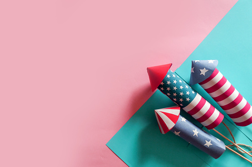 4th July holiday shopping concept. Shopping bags in national american colors and firework rockets