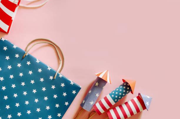conceito da compra do feriado de 4 julho. Sacos de compra em foguetes americanos nacionais das cores e do artifício - foto de acervo