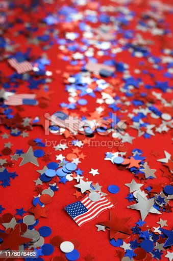 istock 4th of July American Independence Day background . Holiday confetti usa flag colors decorations on red  background. top view, 1178076463