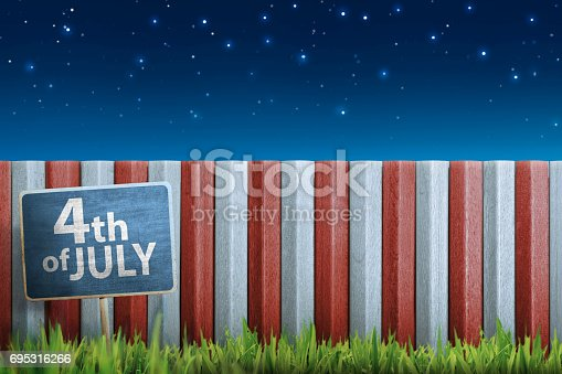 istock 4th of July chalk sign on plank on the grass 695316266