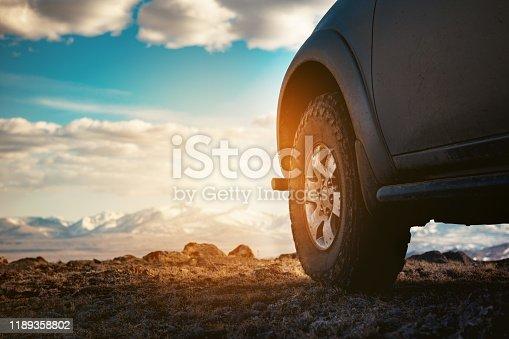 4x4 car wheel at offroad terrain against mountains