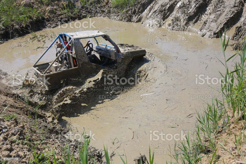 4x4 Offroad car driving through deep mud with water - 4wd car splashing mud and water with big tires stock photo