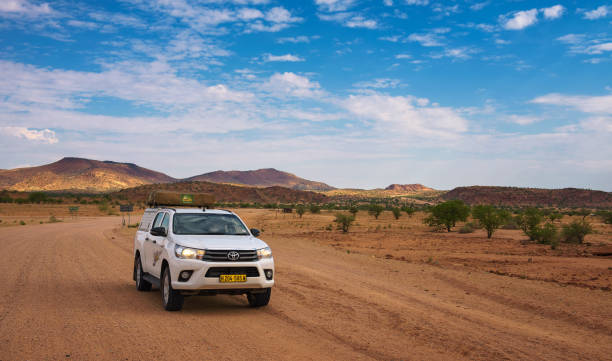 4x4 rental car equipped with a roof tent driving through Damaraland in Namibia stock photo