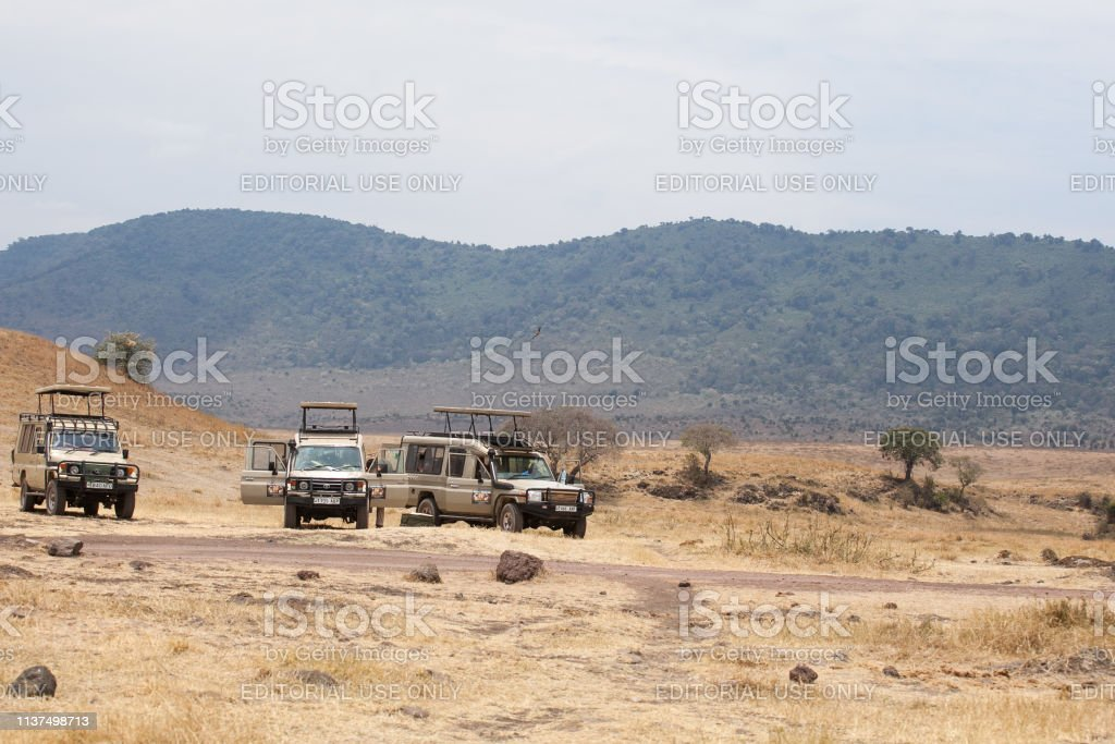 4x4 safari cars parked near an anicent lake at the bottom of...