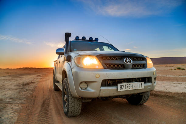 4x4 vehicle without driver in the Moroccan desert under a beautiful sunset stock photo