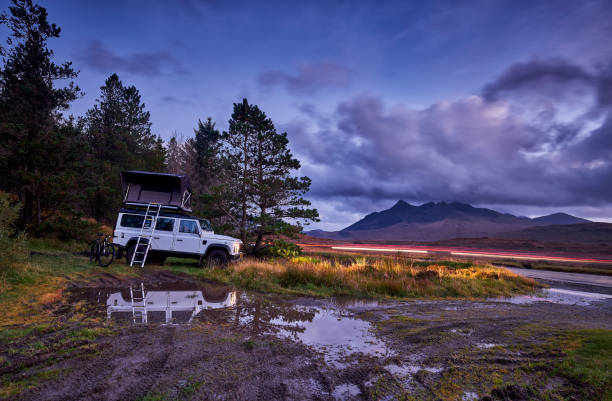 4x4 with roof tent is wild camping. 4x4 with roof tent is wild camping. He is standing near the forest next to the road at dusk. north coast 500 stock pictures, royalty-free photos & images