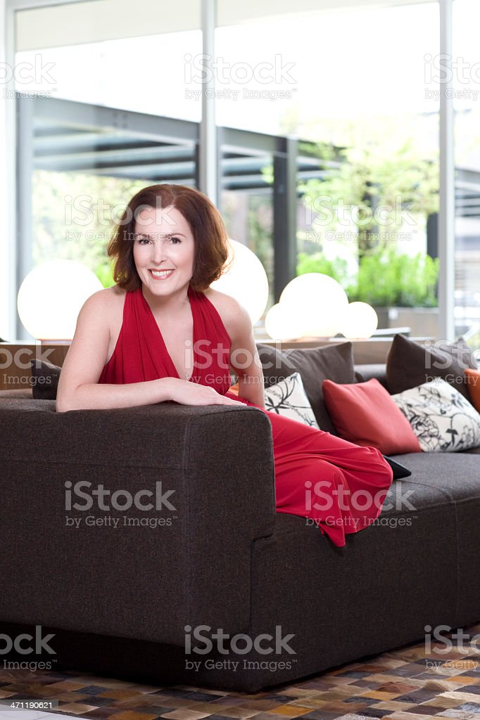 50s Adult Woman Portrait on Modern Couch in Dress, Copyspace stock photo
