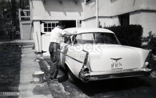 man in dungarees and t-shirt washing a 1957 chevrolet white sedan in his driveway