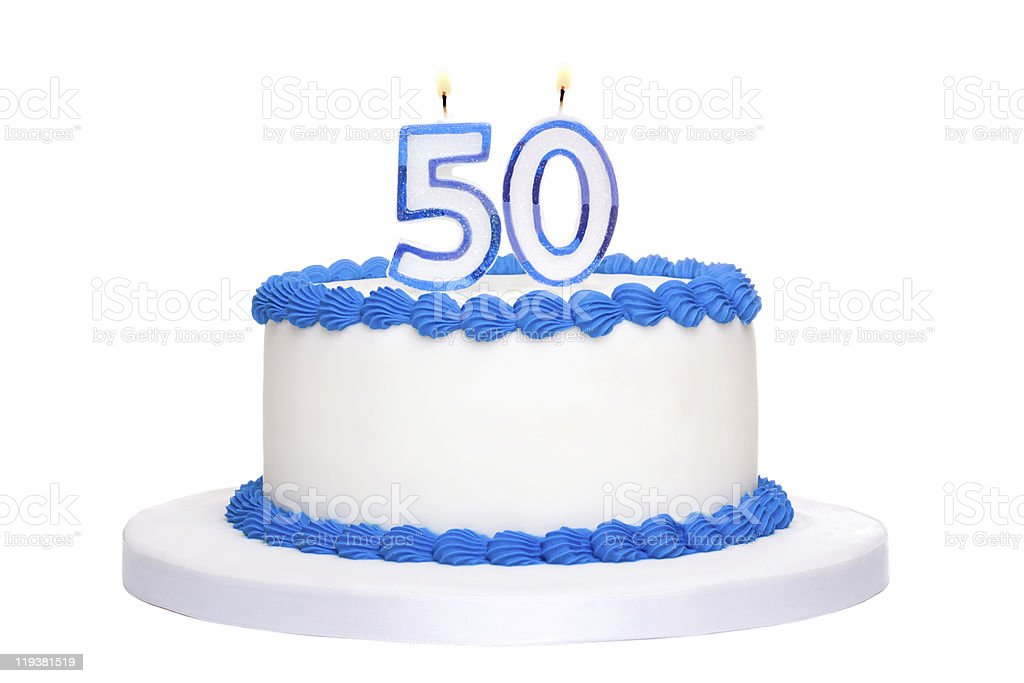 A 50th white birthday cake with blue piping and candles  stock photo