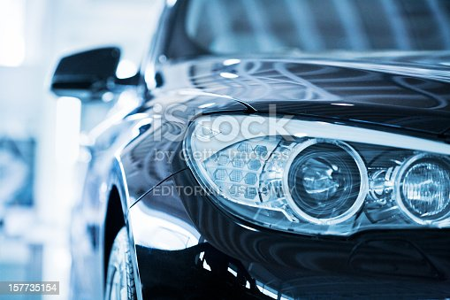 Hamburg, Germany - May 2,  2010 : Close up from the left front of a parking blue BMW 530d. Shallow depth of field with fokus on the headlight. BMW is a German automobile, motorcycle and engine manufacturing company founded in 1916
