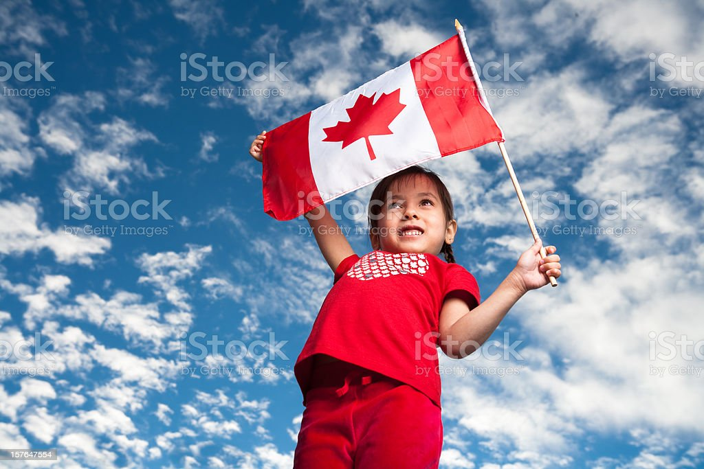 A 5-year-old smiling girl holding a Canadian flag stock photo