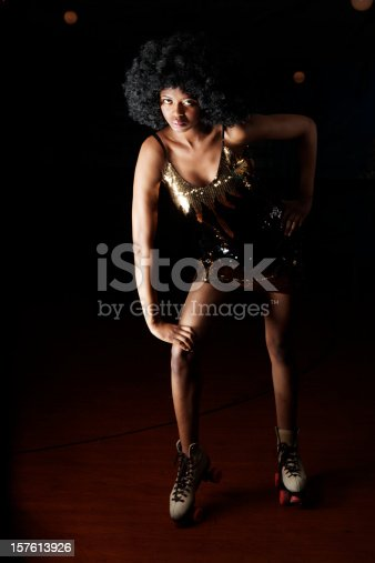 istock 70s style: female African-American rollerskater posing on a roller rink 157613926