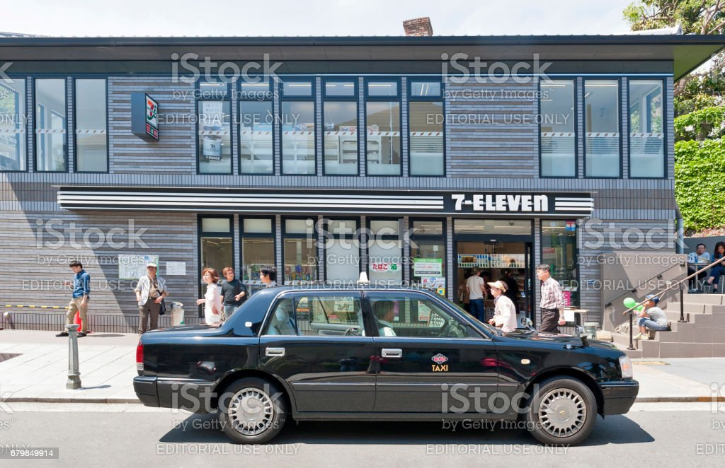 7-Eleven facade in black theme design with a black taxi stopped in front stock photo