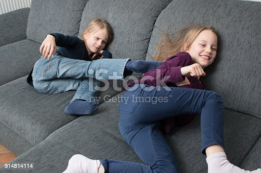 istock 7-jähriges Mädchen tritt ihrer 9-jährigen Schwester in den Rücken 914814114