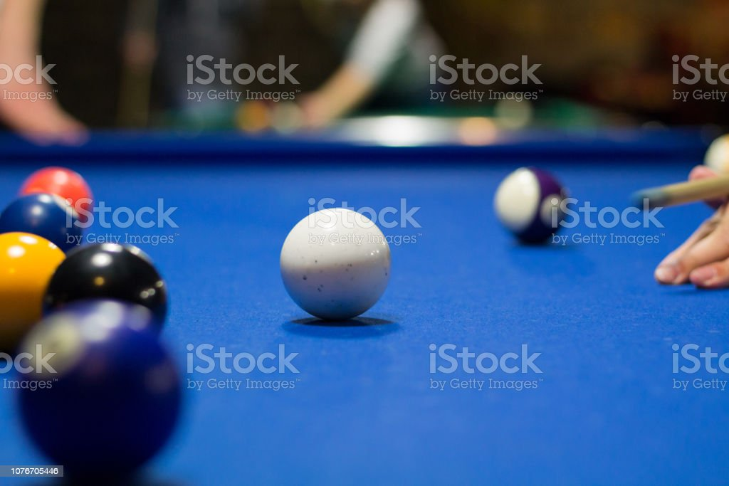 Billiard pool game in progress, player aims to shoot balls with cue