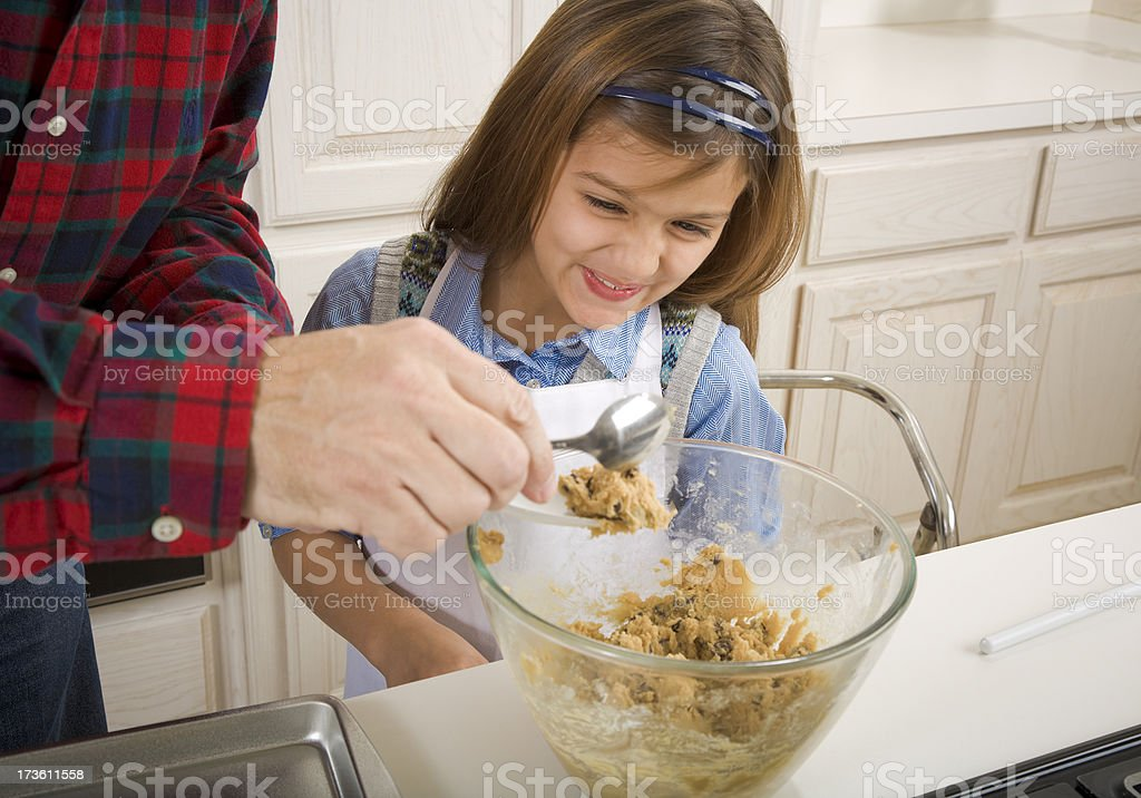 8-year-old daughter baking chocolate chip cookies with dad royalty-free stock photo
