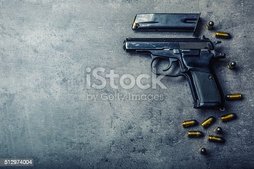 istock 9mm pistol gun and bullets strewn on the table 512974004