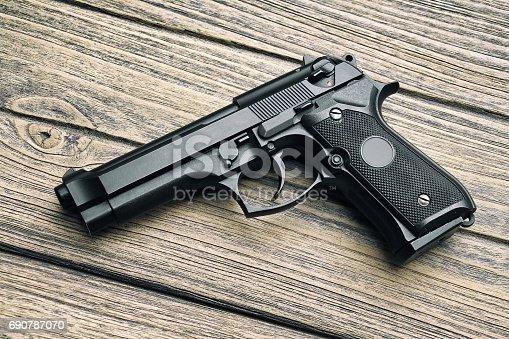 istock 9mm pistol, Gun weapon series, Modern U.S. Army handgun M9 close-up on wooden background. 690787070