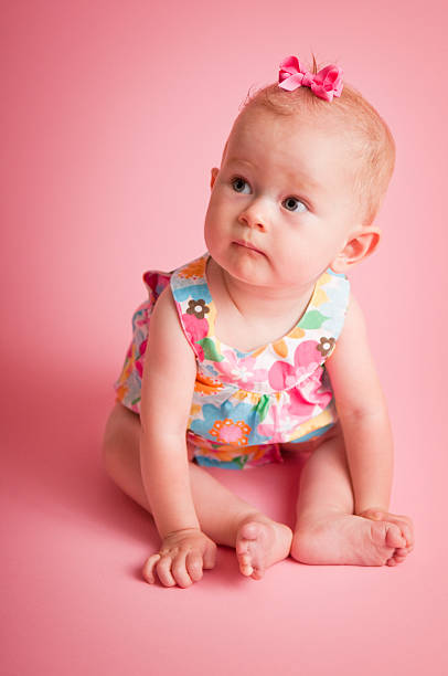9-Month-Old Baby Girl Sitting on Pink Background stock photo