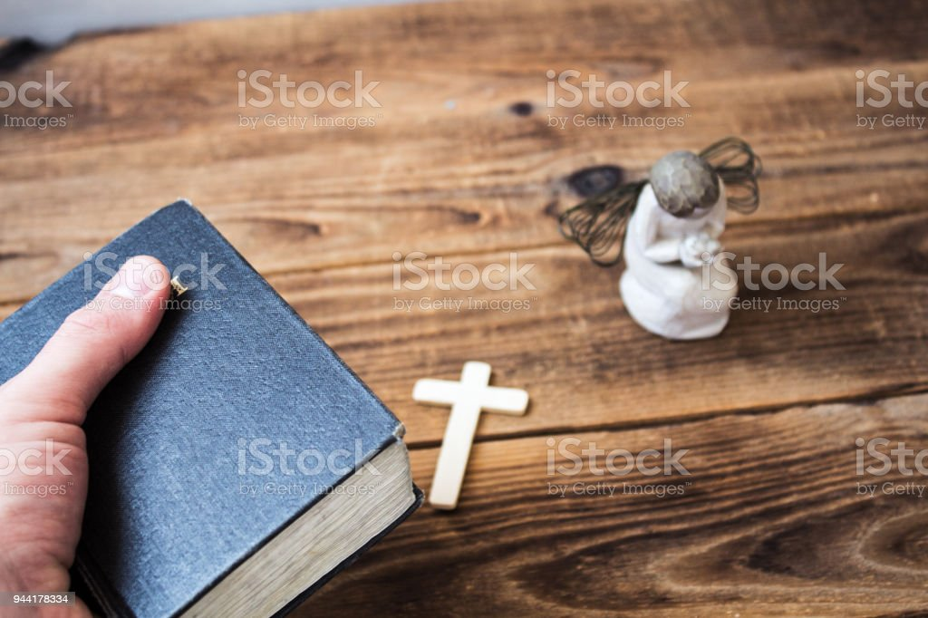 a angel old bible in hand and cross stock photo