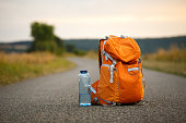 a backpack for an orange camera and a bottle of water on an asphalt road in a field at sunset