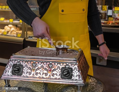 istock a barista man in a yellow apron is making turkish coffee on sand in a turk. 1186143008
