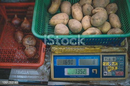 a basket of potato on a scale weighting machine