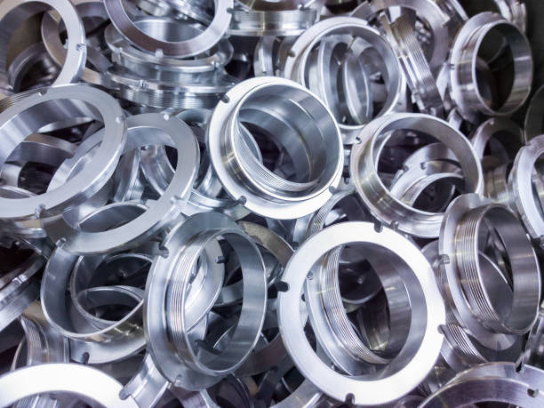 a batch of machined shiny aluminium parts with selective focus stock photo