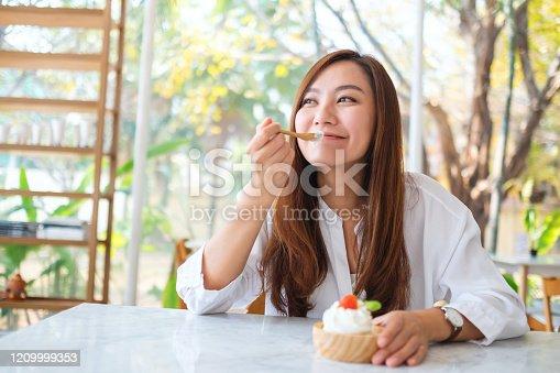 istock a beautiful asian woman enjoy eating an ice cream in restaurant 1209999353