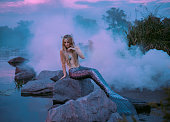 a beautiful mermaid is sitting on the rock in the purple fog