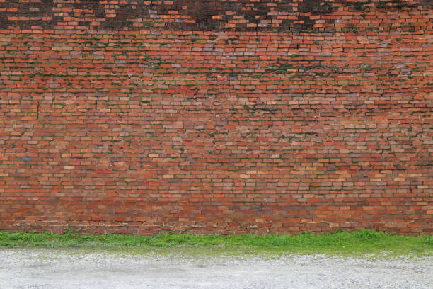 a beautiful old faded natural red brick garden wall lined with green grass next to a fresh raked gravel path perfect for background marketing material as well as wallpaper card poster backdrop stock photo
