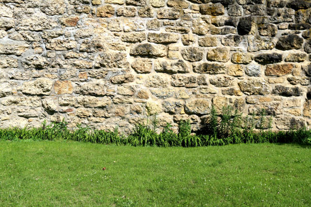 a beautiful old manor house formal garden wall made of vintage stone and rocks lined with bright green grass featuring a freshly landscaped lawn and shadows on a bright sunny summer day stock photo