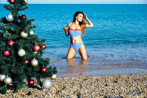 istock a beautiful woman in a swimsuit sea Christmas new year tree vaca 1223450304