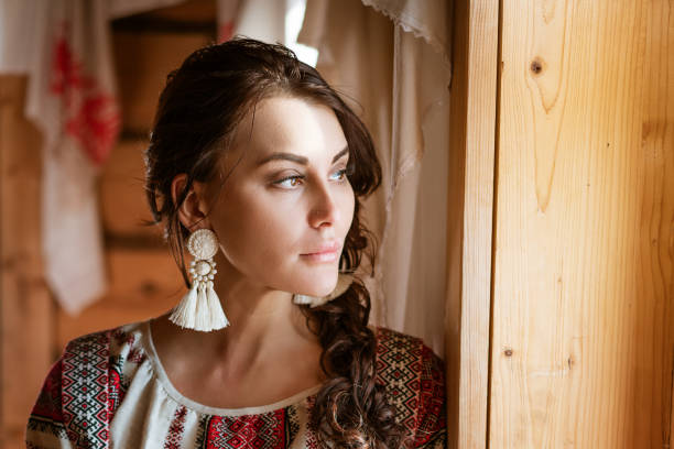 a beautiful woman with a national dress is sitting at the window in the hut stock photo
