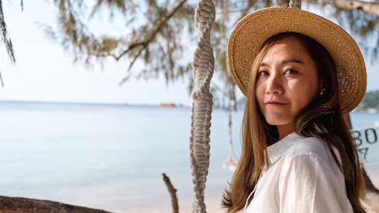 Portrait image of a beautiful young asian woman with swing by the sea