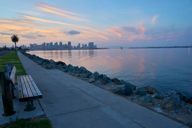 a bench welcomes anyone wishing to watch the glorious sunrises over Coronado Bay, San Diego, California stock photo
