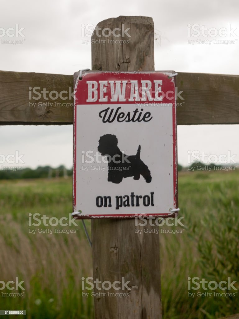 a beware dog patrol sign on wooden fence stock photo