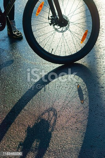 istock a Bicycle wheel on the pavement, shadow of Bicycle on the road 1153460030