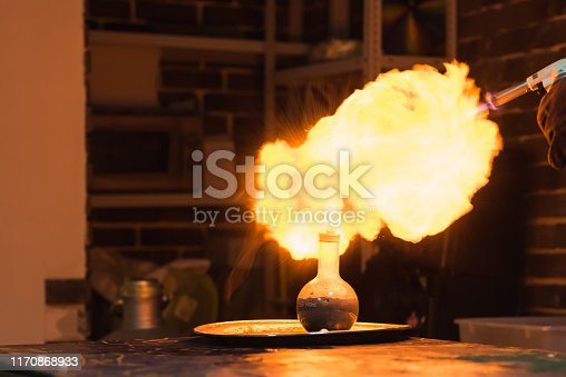 Lab technician setting fire to a ball with hydrogen blowtorch