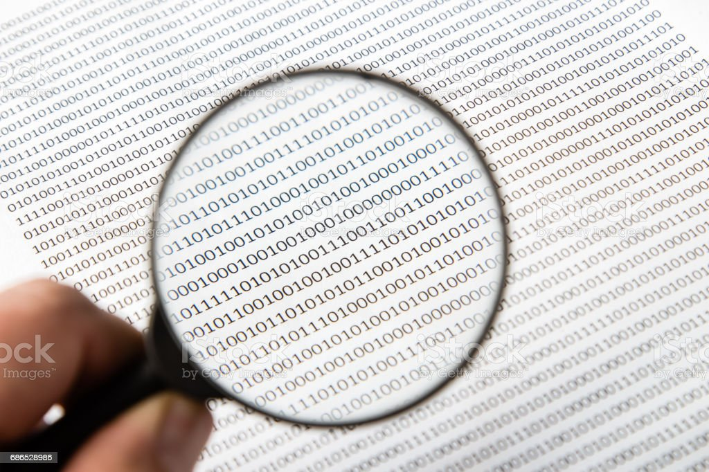 a black and white image of a human scrutinizing software code, this image can be used to represent the function of an antivirus program on a computer. royalty-free stock photo