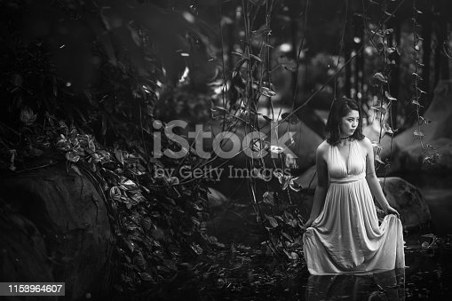 a black and white photo of an asian chinese female standing inside the water pool in the forest looking away