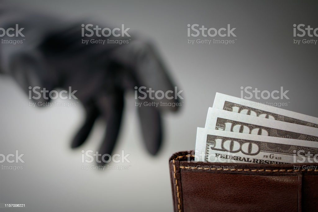 a black-gloved thief steals money from a wallet. concept of danger of...