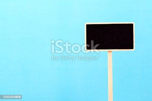 923869178 istock photo a blank blackboard label isolated on a blue background 1040404806
