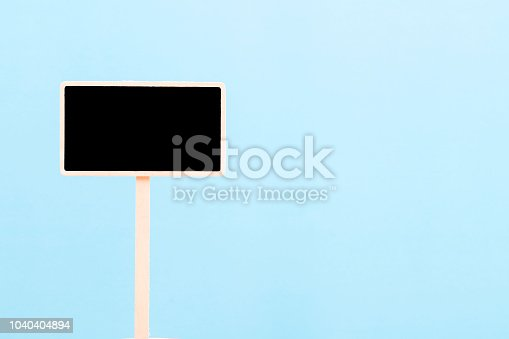 923869178 istock photo a blank blackboard label isolated on a blue background 1040404894