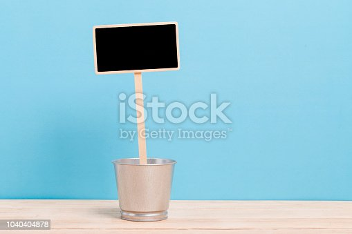 923869178 istock photo a blank blackboard label with iron bucket isolated on a blue background 1040404878